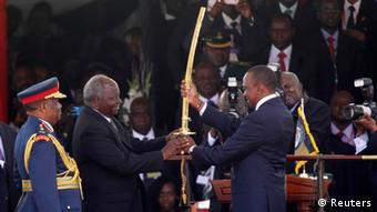 Kenya's President Uhuru receives a special sword representing the instruments of his power and authority from his predecessor Mwai Kibaki Photo:REUTERS/Thomas Mukoya