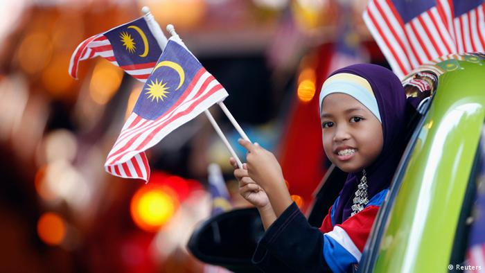 A girl waves Malaysian national flags as she participates in a parade during the double celebrations of Malaysia Day and Independence Day in Kuala Lumpur, in this September 16, 2011 file photograph. To match the latest quarterly Thomson Reuters/INSEAD Asia Business Sentiment Survey ASIA-COMPANIES/SENTIMENT/ REUTERS/Bazuki Muhammad (MALAYSIA - Tags: SOCIETY POLITICS ANNIVERSARY)