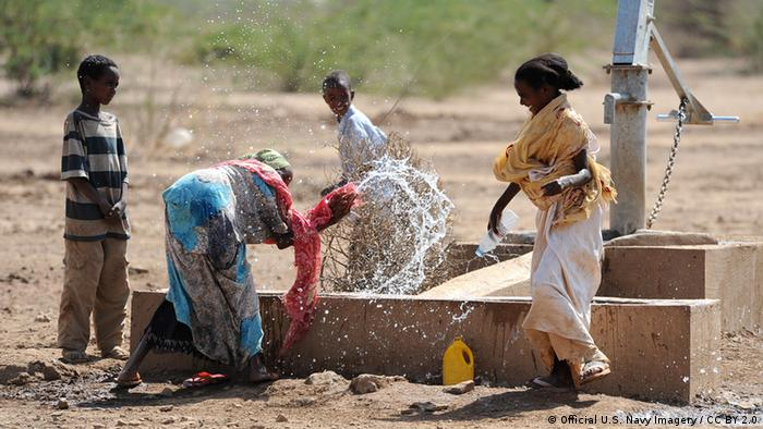 Ethiopian children play in the water of a well built by Sailors.