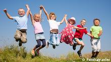 Glückliche Kinder halten sich an den Händen uns springen gemeinsam in die Luft