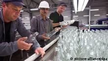 Die Altmärker Oliver Schulz (l) und Christian Krziwhnie (r) arbeiten am Mittwoch (18.05.2011) gemeinsam mit dem Inder Karisma Kapoor (M) an einer Taktstraße für Flaschen der Agenda Glas AG in Gardelegen (Altmarkkreis Salzwedel). Das börsennotierte indische Unternehmen Hindusthan National Industries and Glas wird alle 150 Arbeitnehmer und den Geschäftsbetrieb an dem altmärkischen Standort weiterführen. Die im Jahr 2008 gegründete Agenda Glas AG betreibt dort auf einer 16,7 Hektar großen Fläche eine der modernsten Glashütten zur Herstellung von Behälterglas. Die Hindusthan National Industries and Glas mit Hauptsitz in Kolkata erwirtschaftete im vergangenen Jahr einen Umsatz von rund 219 Millionen Euro. Foto: Jens Wolf dpa/lah +++(c) dpa - Bildfunk+++ pixel