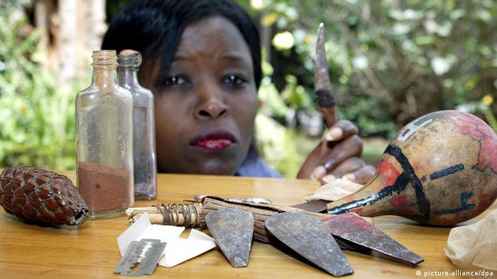 A Kenyan woman contemplates the instruments used to perform FGM