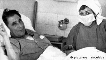 Homem deitado numa cama ao lado e uma mulher com roupas de enfermagem