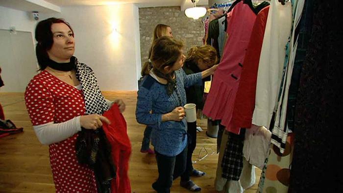 Frauen schauen sich Kleider an, die auf einer Stange hängen.