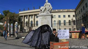 A student holds a sign saying My house, my university, my first semester, camping out in front of Humboldt University