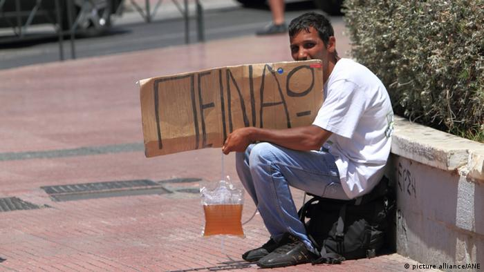 Beggar with cardboard sign sits in street . (Photo: Picture Alliance / ANE)