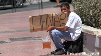 Man begging in Athens with sign saying 'I'm hungry' in Greek (Photo: source unknown)