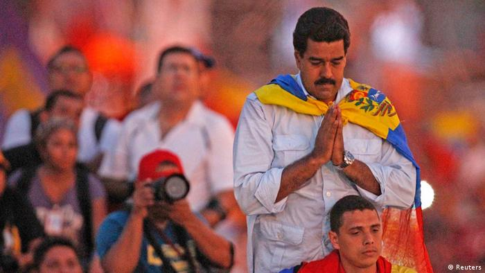 Venezuela's acting President and presidential candidate Nicolas Maduro (top R) pauses to pray as he arrives at his closing campaign rally in Caracas April 11, 2013. Venezuela will hold its presidential elections on April 14. REUTERS/Tomas Bravo (VENEZUELA - Tags: POLITICS ELECTIONS)