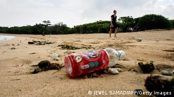 A tourist walks along a beach littered with seaweeds and plastic bottles near the venue of the UN Climate Change Conference 2007 in Nusa Dua, on Bali island, 04 December 2007. (Photo: JEWEL SAMAD/AFP/Getty Images)