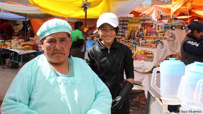 A woman wearing a green apron and hat on the left, a young girl in a white hat on the right (photo: Sara Shahriari)