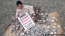 Die am Mittwoch (13.08.2010) in Berlin gestellte Szene zeigt eine symolische Steinigung, bei der eine Frau ein Schild mit der Aufschrift Stop Stoning and Execution hält. Die Frau nahm an einer Protestkundgebung vom Nationalen Widerstandsrat Iran (NWRI) teil, die sich gegen die Hinrichtungen politischer Gefangener, Folter und Steinigung richtet. Foto: Stephanie Pilick dpa/lbn