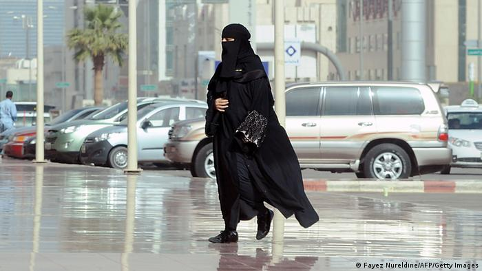 A Saudi woman wearing a black headscarf and black robes arives at a shopping mall, with parked cars in the background. Copyright: FAYEZ NURELDINE / AP