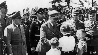 Adolf Hitler (1889 - 1945) receives bouquets from children at the planned Volkswagen factory in Fallersleben, where he is about to lay the foundation stone, 27th May 1938. Accompanying Hitler are Dr. Robert Ley (1890 - 1945), Heinrich Himmler (1900 - 1945) and Viktor Lutze (1890 - 1943). (Photo by Keystone/Hulton Archive/Getty Images)