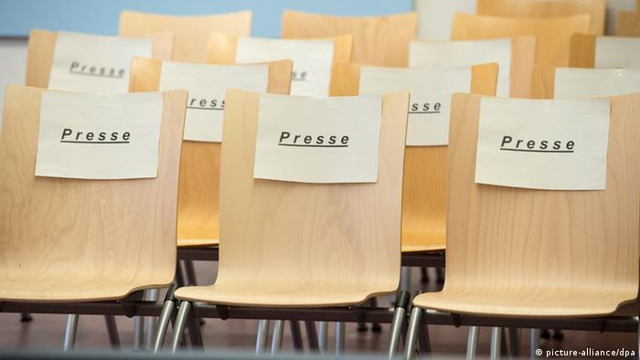 A picture of chairs with paper labels saying Presse (press) on them in a Munich courtroom.