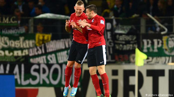 Jonathan Schmid and Daniel Caligiuri celebrate the third Freiburg goal in their 3-1 win over Hannover.