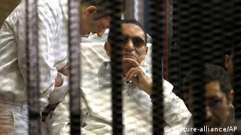 epa03660527 Gamal Mubarak (L) and brother Alaa Mubarak (R), with their father former Egyptian President Hosni Mubarak in a cage inside the court room during his trial at the Police Academy in Cairo, Egypt, 13 April 2013. A judge presiding over the retrial of former Egyptian president Hosny Mubarak on charges related to the 2011 deaths of protesters withdrew from the case as it started 13 April 2013. Judge Mustafa Hassan said as the new trial started that he was feeling 'uneasiness' about hearing the case and would refer the case back to the Appeals Court so it could name a new judge. EPA/KHALED ELFIQI