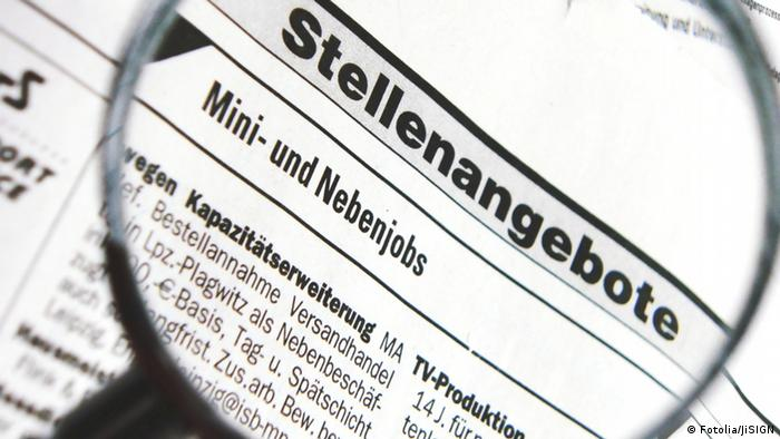 Durch eine Lupe sieht man Stellenangebote für Mini- und Nebenjobs in einer Zeitung.