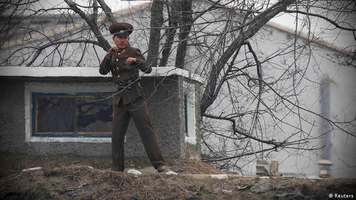A North Korean soldier practices boxing moves in front of a guard tower on the banks of the Yalu River, near the North Korean town of Sinuiju, opposite the Chinese border city of Dandong