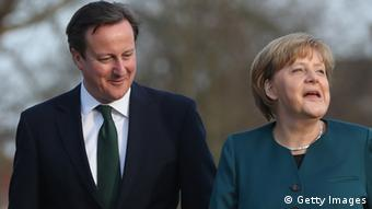 British Prime Minister David Cameron speaks with German Chancellor Angela Merkel during a stroll in the garden following his arrival at the Meseberg government guest house on April 12, 2013 in Meseberg, Germany. (Photo by Sean Gallup/Getty Images)