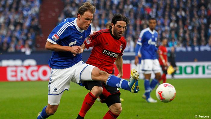 Bayer Leverkusen's Benedikt Hoewedes tackles Schalke 04's Gonzalo Castro (R) during the German first division Bundesliga soccer match in Gelsenkirchen April 13, 2013. REUTERS/Ina Fassbender (GERMANY - Tags: SPORT SOCCER) DFL RULES TO LIMIT THE ONLINE USAGE DURING MATCH TIME TO 15 PICTURES PER GAME. IMAGE SEQUENCES TO SIMULATE VIDEO IS NOT ALLOWED AT ANY TIME. FOR FURTHER QUERIES PLEASE CONTACT DFL DIRECTLY AT + 49 69 650050