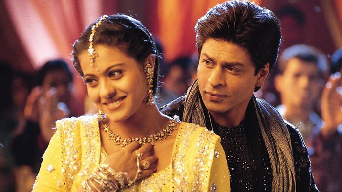 Ein Paar in indischer Kleidung. Er steht hinter ihr, und sie guckt lächelnd weg.