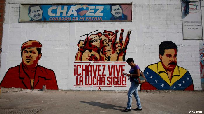 A woman walks past a mural depicting Venezuela's acting President and presidential candidate Nicolas Maduro (R) and Venezuela's late President Hugo Chavez in Caracas April 12, 2013. Chavez's self-declared socialist revolution will be put to the test at a presidential election on Sunday that pits Maduro, his chosen successor, against a younger rival promising change in the nation he polarized. The mural reads in Spanish, Chavez lives, the fight goes on!. The banner on top reads, Chavez, heart of my country. REUTERS/Tomas Bravo (VENEZUELA - Tags: POLITICS ELECTIONS TPX IMAGES OF THE DAY)