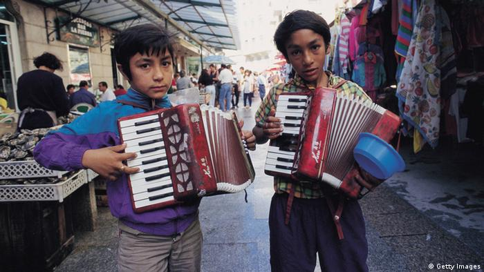 Infantile mendicity Two children musicians beg in a street market (Photo by Sofia Moro/Cover/Getty Images)