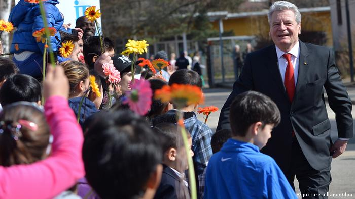 German President Joachim Gauck greeted by children at a ceremony commemorating the 60th anniversary of the German asylum center Marienfelde.Foto: Britta Pedersen/dpa