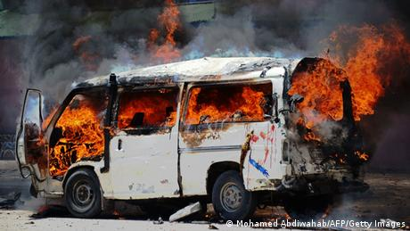 A min bus is engulfed in flames following a bomb attack in Mogadishu.
