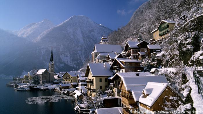 A collection of snow-covered rooftops nestled on the side of a mountain next to a lake