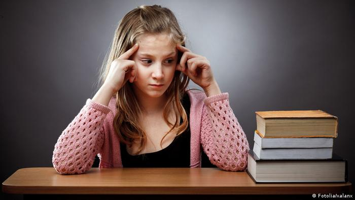 Unhappy caucasian schoolgirl at her desk, near a stack of books