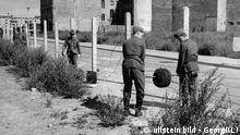 Deutschland / DDR, Berlin Mauerbau. DDR-Grenztruppen verlegen Stacheldraht an der Sektorengrenze. August 1961 Germany / GDR, Berlin. The building of the wall. East-German soldiers setting up barbwire at the border. August 1961 ullstein - Georgi(L)