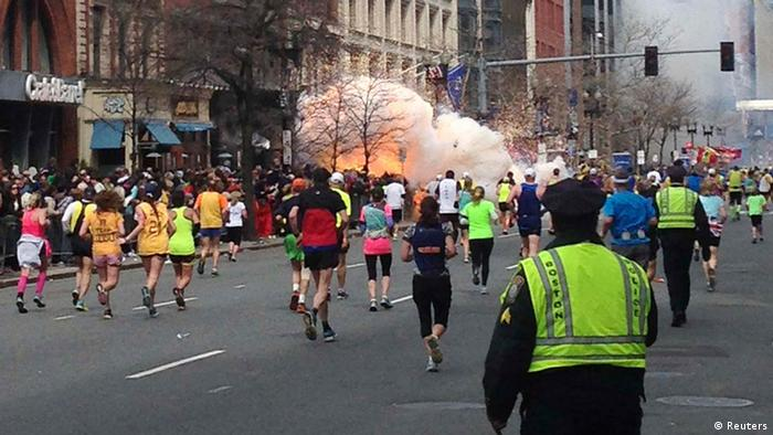 Runners continue to run towards the finish line of the Boston Marathon as an explosion erupts near the finish line of the race in this photo exclusively licensed to Reuters by photographer Dan Lampariello after he took the photo in Boston, Massachusetts, April 15, 2013. Two simultaneous explosions ripped through the crowd at the finish line of the Boston Marathon on Monday, killing at least two people and injuring dozens on a day when tens of thousands of people pack the streets to watch the world famous race. REUTERS EXCLUSIVE REUTERS/Dan Lampariello (UNITED STATES - Tags: CRIME LAW SPORT ATHLETICS TPX IMAGES OF THE DAY ) MANDATORY CREDIT