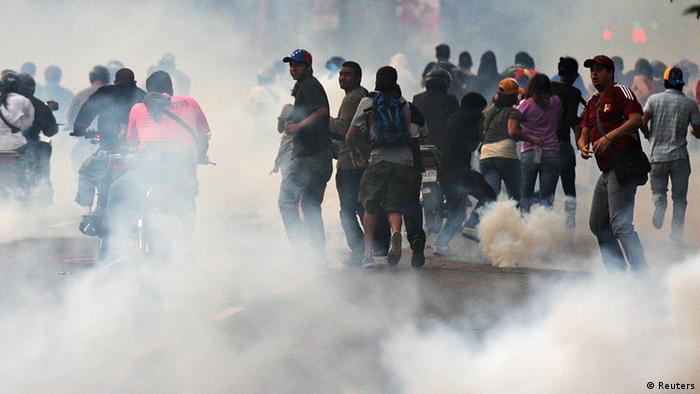 Supporters of opposition leader Henrique Capriles run from tear gas fired by riot police as they demonstrated for a recount of the votes in Sunday's election, in Caracas, April 15, 2013. Hundreds of protesters clashed with police in the Venezuelan capital on Monday after Capriles called for demonstrations to demand a recount of votes from Sunday's election to replace the late Hugo Chavez. Photo: REUTERS/Christian Veron