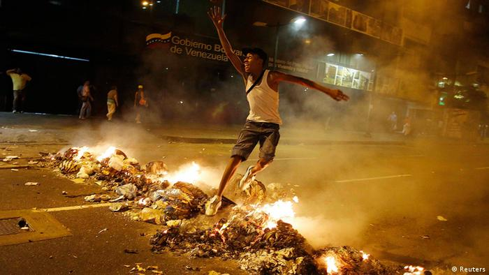 A man jumps with a ball over a barricade of burning garbage that supporters of opposition leader Henrique Capriles used to block a street, as they demonstrated for a recount of the votes in Sunday's election, in Caracas, April 15, 2013. (Photo: Reuters/Tomas Bravo)