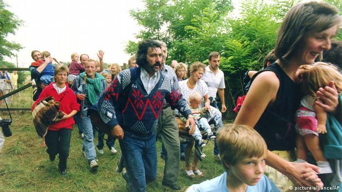 DDR-Bürger überqueren auf einer Wiese die ungarisch-österreichische Grenze