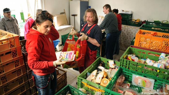 Kisten voller Lebensmittel und Menschen bei einer Tafel.