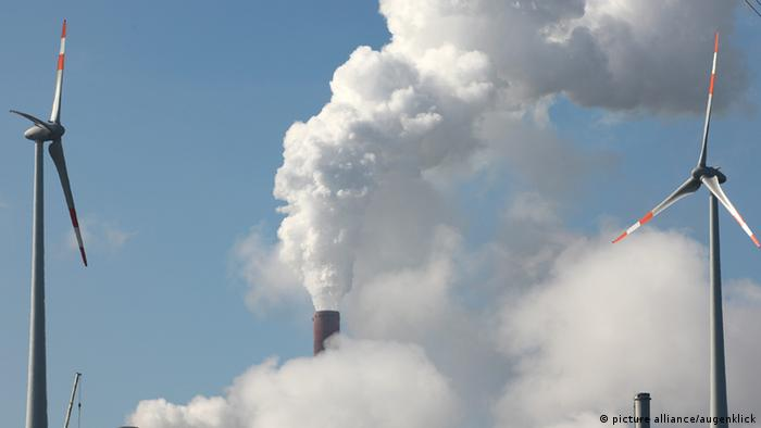 Fumes from a coal-fired power plant rise behind two wind turbines (c) picture-alliance/augenklick