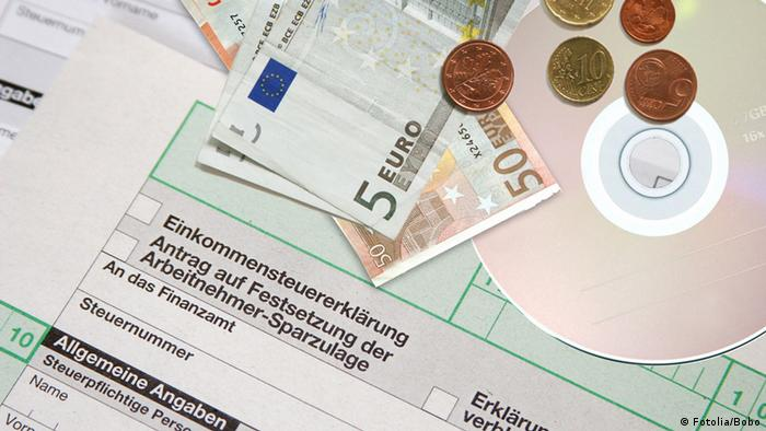 A symbolic image showing a German tax return form, partially covered with some euro curency notes and coins, and a CD.