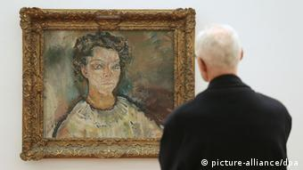 An elderly man wearing a black jacket and whose back faces the camera admires a portrait of a young woman framed in gold.