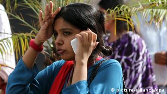 epa03664016 A local woman worker uses her mobile phone after she was evacuated along with hundreds of other workers in Karachi, Pakistan 16 April 2013 -- a city nearest the border with Iran where a 7.8 magnitude earthquake struck. Early reports suggest that 40 have so far died but there is no information on damage. EPA/REHAN KHAN +++(c) dpa - Bildfunk+++