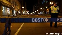 BOSTON, MA - APRIL 16: A Boston police officer stands near the scene of a twin bombing at the Boston Marathon, on April 16, 2013 in Boston, Massachusetts. Three people are confirmed dead and at least 141 injured after the explosions went off near the finish line of the marathon yesterday. The bombings at the 116-year-old Boston race, resulted in heightened security across the nation with cancellations of many professional sporting events as authorities search for a motive to the violence. (Photo by Spencer Platt/Getty Images)