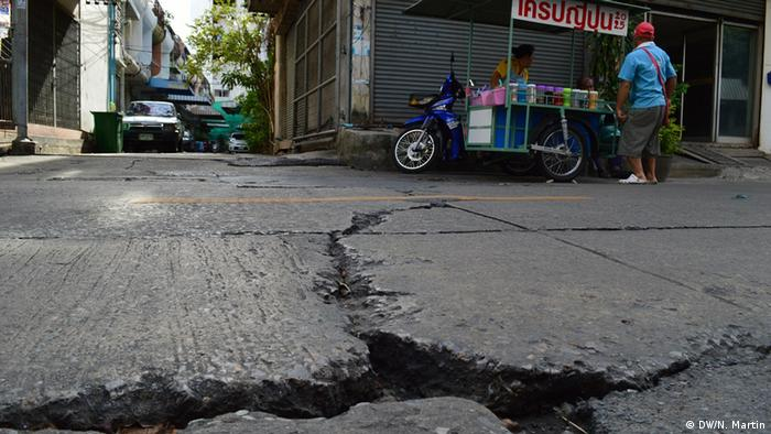A woman sells Thai street food inches from the huge cracks left by floods in a Bangkok street (photo: DW/ Nik Martin)