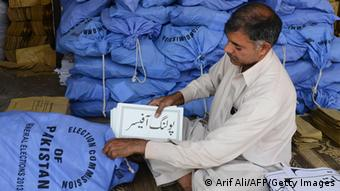 Pakistani election commission worker packs documents for polling stations ( Arif Ali/AFP/Getty Images)