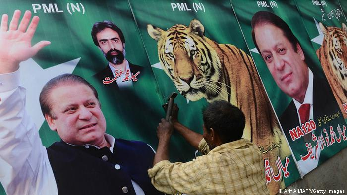 A Pakistani worker fixes billboards featuring photographs Nawaz Sharif in Lahore on April 9, 2013. Opinion polls are notoriously unreliable in Pakistan, but indicators suggest Sharif is likely to emerge the biggest winner from the general election on May 11, which will mark the country's first democratic transition of power. AFP PHOTO/ ARIF ALI (Photo credit should read Arif Ali/AFP/Getty Images)
