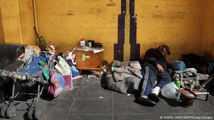A homeless man sleeps in front of La Bombonera stadium in Buenos Aires' La Boca neighbourhood, on August 21, 2009. La Boca is widely known for the football club Boca Juniors - the most popular in the country, for Caminito Street and its colorful houses, for the most polluted river in the country, the Riachuelo, and for its poverty. AFP PHOTO/Daniel GARCIA (Photo credit should read DANIEL GARCIA/AFP/Getty Images)