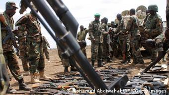 Photo taken September 22, 2012 shows AU soldiers from Uganda looking at some of the weapons recovered from members of Somalia's Al-Qaeda-linked Shebab after they gave themselves up to African Union Mission in Somalia (AMISOM) forces in Garsale, some 10km from the town of Jowhar, 80km north of the capital Mogadishu. Over 200 militants disengaged following in-fighting between militants in the region in which eight supporters of Shabaab were killed, including two senior commanders. The former fighters were peacefully taken into AMISOM's protection handing in over 80 weapons in the process, in a further indication that the once-feared militant group is now divided and being defeated across Somalia. Deputy Force Commander of AMISOM Operations, Brigadier Michael Ondoga said a number of militants have contacted the AU force indicating their wish to cease fighting and that they their safety is assured if they give themselves up peacefully to AMISOM forces. AFP PHOTO/ MOHAMED ABDIWAHAB (Photo credit should read Mohamed Abdiwahab/AFP/GettyImages)