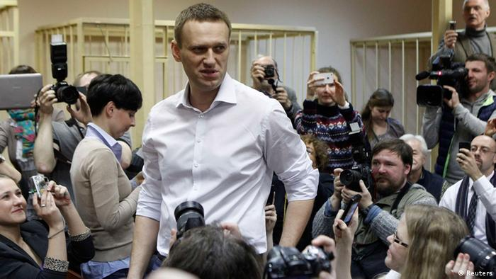 Russian opposition leader and anti-graft blogger Alexei Navalny (C) looks on surrounded by journalists after arriving for a court hearing in the city of Kirov April 17, 2013. Russian protest leader Navalny, looking calm and relaxed, went on trial on Wednesday on theft charges which he says are politically motivated and part of a clampdown on dissent by Vladimir Putin. REUTERS/Maxim Shemetov (RUSSIA - Tags: POLITICS CRIME LAW)