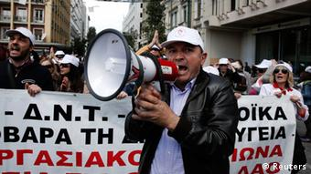 A man with a megaphone stands in front of a banner at a Greek demonstration
