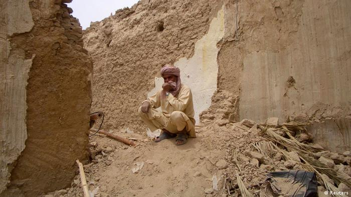 A survivor of Tuesday's earthquake sits on the rubble of his mud house after it collapsed following the quake in the town of Mashkeel, southwestern Pakistani province of Baluchistan, near the Iranian border April 17, 2013. The powerful earthquake struck a border area of southeast Iran on Tuesday killing at least 35 people in neighbouring Pakistan, destroying hundreds of houses and shaking buildings as far away as India and Gulf Arab states. REUTERS/Shah Nazar (PAKISTAN - Tags: DISASTER)